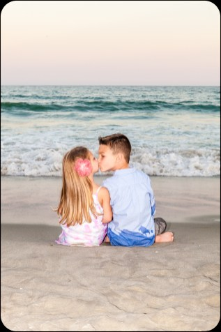 Children kissing at sunset on the beach.