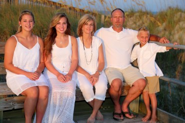 family on bench at the beach
