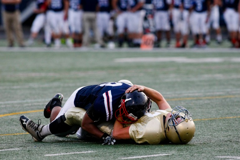 Quarterback Raymond Spangler rests on the ground after a sack from Bishop Hartley lineman John Anderson.