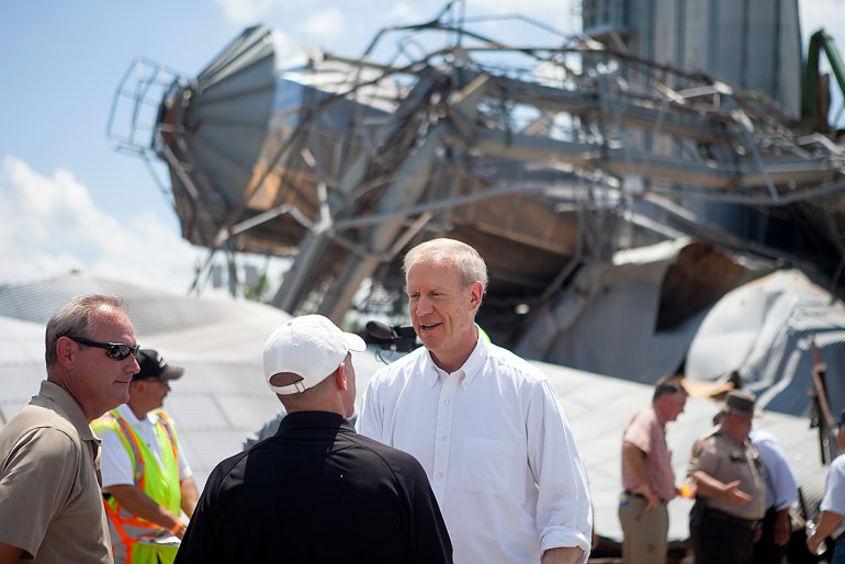 Illinois Governor Bruce Rauner talks with emergency officials in front of heavily damaged grain bins during a stop in Cameron on Friday. The community was struck by an EF2 tornado on Thursday night, damaging over 50 homes. STEVE DAVIS/The Register-Mail