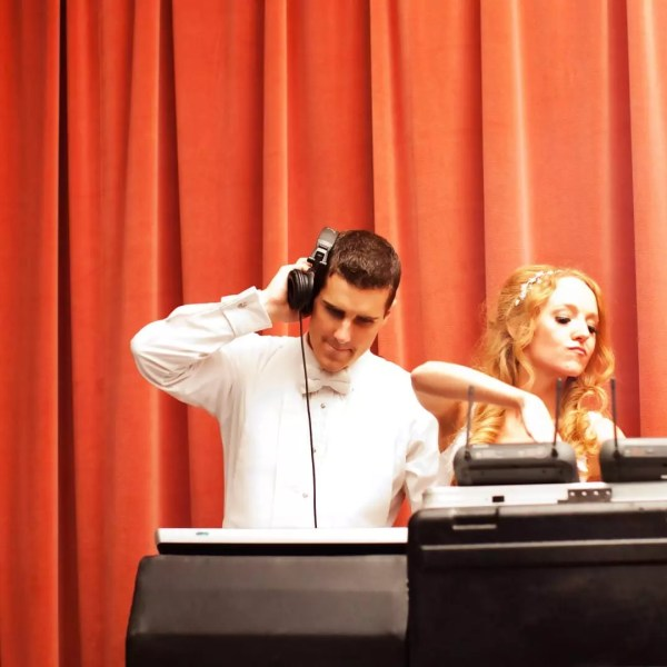 A newlywed couple enjoy DJing music on their wedding day