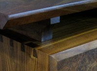 Dovetails strengthen the solid wood carcasse while mitering helps the desktop seem to float.