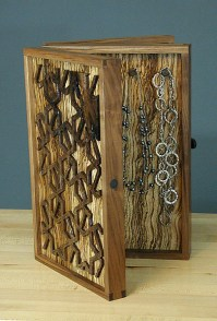 Necklaces hang from hand-carved walnut hooks.