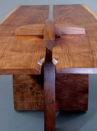 Tops fitted into grooves in the cross-piece trestle and buttery walnut curves.