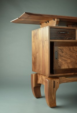 Through dovetails and mortise-and-tenon joints complement Chinese legs and a floating top.