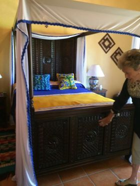 Woman showing hand carved bed footer in Mexico