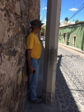 Man standing next to a pole on the sidewalk in Mexico