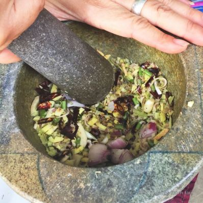 Mashing herbs and spices to prepare the red curry paste, Thai cooking class