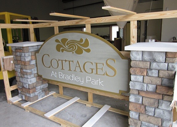 Cottages 3-D Embossed Sign Panels Suspended Between Faux Block Stone Columns Before Shipping