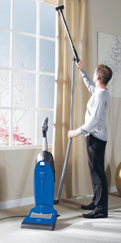 The Miele S7210 Twist is one of the most in demand upright vacuum cleaners from this popular brand. Built to last and meant as a true investment, the Miele brand has established itself in the area of top of the line vacuums.  Save $50 off the Twist right now at Amazon. Daily Use For day to day use, the Miels Twist is very easy to use. First it has a patented swivel technology that makes it easy to steer. This is practically essential in any upright vacuum, as they can be quite cumbersome to maneuver, especially around corners and furniture. Not only can it move in any direction, it can also lay flat to get under low furniture like beds and couches.  To make it even easier to steer, push and pull, the wheels on the front rotate a full 360 degrees, meaning it really does swivel. The wheels are also non-marking, so they won't leave smudges on hardwood floors and linoleum.  As far as the floor types the Miele S7210 works best for, it works very well on them all. Instead of having a switch or dial you need to flip or turn to change the height of the base plate, the adjustment for height is completely automatic. In other words, the Twist detects the type of carpet of bare floor and adjusts accordingly.  You can also easily turn off the roller brush so small bits won't get flung around on your hardwood or other bare floors. (If you have a kitty litter box in the house, you'll really appreciate this feature.) This will also protect your finely finished bare floors from getting scratched by the brush.  One of the other features users comment on in their reviews is something that is complained about quite a bit in other uprights with an extension hose and tools like the Shark Rotator and Navigator. That is that the machine has a tendency to want to tip over when the hose is stretched out all the way. Miele has thought of this and incorporated an anti-tipping device so the machine remains stable even when you stretch out the hose.  Mechanics miele s7210This popular vac has a powerful 1200 watt motor with a separate 4800 RPM motor for the brush motor, meaning it can spin fast and strong enough to get out even deep down dirt from deep pile shag carpets.  Even though it works great on carpet, it can be used for any type of surface without fuss, as the height adjustment is automatic. The way it cleans different types of floor surfaces varies to make sure they get as clean as possible.  It has what's called an electrobrush in the head which incorporates an agitator roller brush to separate carpet fibers so it can suck out dirt that is embedded deep down. This brush is spring-loaded and flexible to adapt to different floor types.  It also has a dial on the top front of the unit for different speeds of the brush depending on how strong you want it to be. It has separate settings for low pile carpet, deep pile carpet, smooth surfaces and curtains or other fabrics.  The Miele S7210 comes complete with a powerful sealed air system, ensuring those find particles of dust, pollen, mold and pet dander end up in the vacuum instead of back in the air. Adding a HEPA filter is available as an option on the Twist.  Tools & Accessories miele twist speed controlDusting brush Upholstery Tool Crevice nozzle Specs Cord length: 39' Extension hose length: 12' Extension wand length: 3' Cleaning radius: 54' Weight: 21.6 pounds Power: 1200 watts with a 4800 r.p.m. agitator brush Voltage: 120v Warranty: 7 years (motor); 7 years (casing); 1 year (all other components) Product Manual Pros miele twistWorks great on all floor surfaces and adjusts automatically Great at getting close to edges and baseboards Does a good job on pet hair, even on furniture Bags are cloth instead of paper, and dust doesn't escape when changing them Cons miele twist changing bagWhile many people prefer a bagged vacuum cleaner like the Miele S7210, some users when they review the model say they don't want to spend the extra money on bags. Amazon actually sells the bags for under $20, and that includes 4 bags plus filters. Bags should be changed once the indicator light comes on or whenever you notice a loss of suction. Reviews do comment that the bags are large so don't need to be changed so often.  Consumer Ratings Overall in user reviews, people who bought and use the Miele S7210 Twist give it a 4 out of 5 star rating. They love that it has all the power of a monster full-size vacuum but is very easy to steer and maneuver. It works just as well on pet hair on your couch as it does on the curtains or glossy hardwood floor. The height adjusts automatically for every type of floor surface, and there are 4 adjustments for speed as well as an option to turn off the brush roll.  If you're someone who doesn't want to hassle with the bags, the Dyson DC65 is also a great choice, but if you're looking for a very powerful bagged full-size upright, the Twist is a great option as well as a great investment and value. Right now, Amazon has the Twist on sale for 10% off.