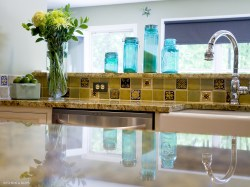 Reflective view of a kitchen counter surface looking at flowers and tile backsplash
