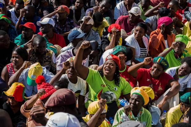 Supporters of Zimbabwe's ruling ZANU PF party salute with clenched fists at the party headquarters on August 30, 2017 in Harare, in a show of support for first lady Grace Mugabe