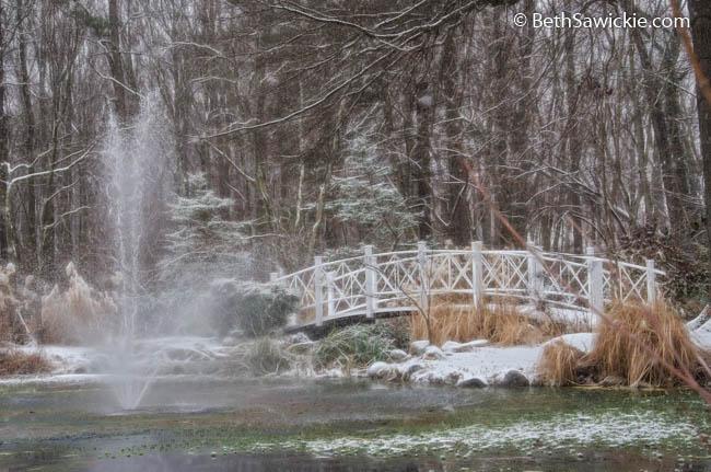 Bridge Across Pond During Winter Snowfall at Sayen Gardens