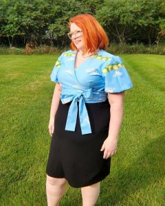 Red Hair with a blue wrap top and straight black skirt