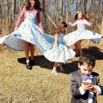 Three girls twirling joyfully in their blue floral skirts made by Beth Smith Textiles.