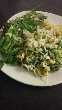 Pesto pasta with peas, spinach and cashew nuts with a rocket salad