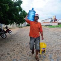 Pintor Antônio Francismar Alves Pereira Batista, 37, morador do Morro do Urubu, enche galões de água nas bicas disponibilizadas pelo empresário Luís Altino que tem um poço na própria casa (Fernando Frazão/Agência Brasil)