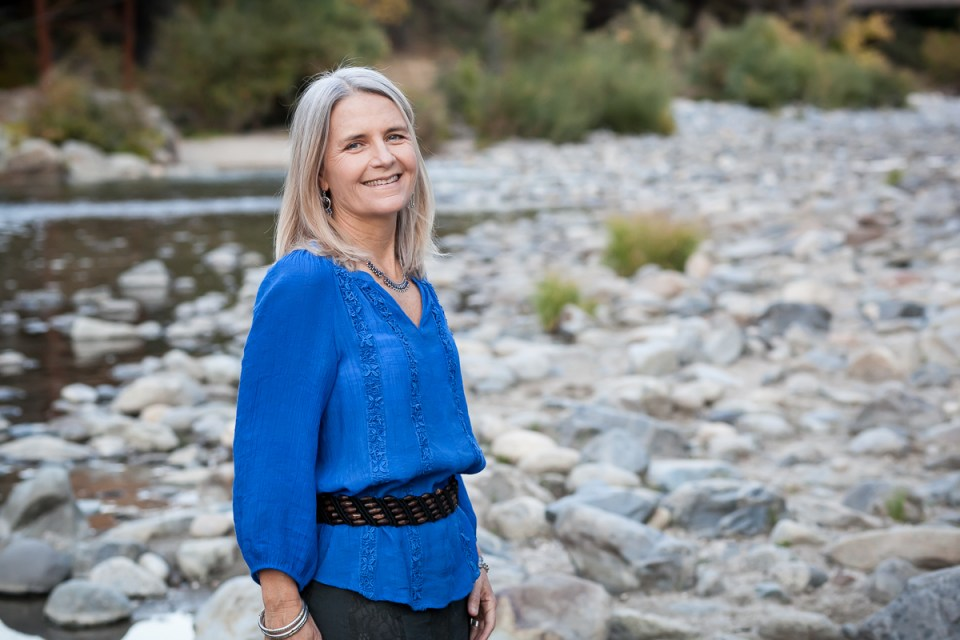 Betsy standing by river in a blue shirt