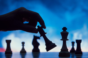 Silhouette of hand moving a chess piece