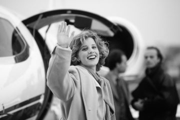 Young woman waving hand and smiling