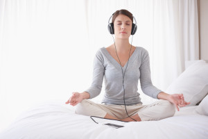 lotus position on bed with headphones