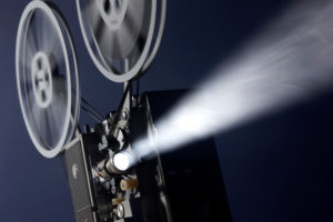 Vintage 16 mm movie projector projecting images through smoky background