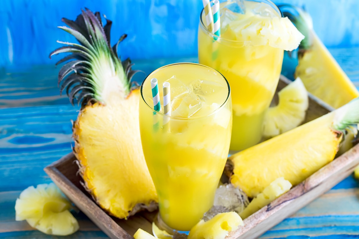 Pineapples and glasses of pineapple smoothie