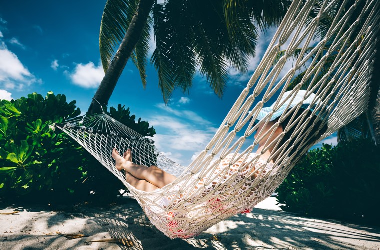 Woman relaxing in the shade of palms on a hammock.