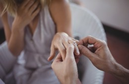 Man putting engagement ring on womans hand