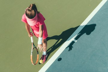 Woman about to serve playing tennis