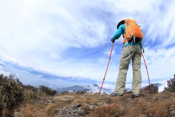 hiker on beautiful rolling clouds mountain peak
