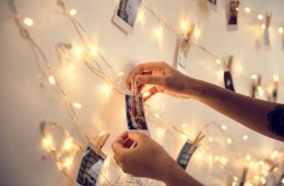 Closeup of hands with photos hanging with decoration lights on t