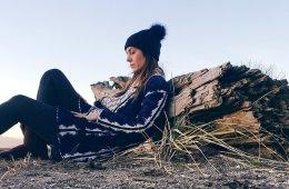 Woman sitting on beach alone