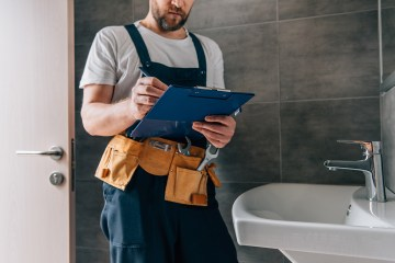 partial view of male plumber with toolbelt writing in clipboard