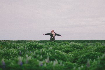 Woman in field with arms out