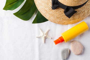 Summer background. Hat, seashells, sunscreen on a white towel. Copy space.