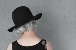 Lady with gray hair in black hat