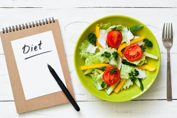 Healthy eating and Diet concept. Green Plate with fresh vegetables salad on wooden table.