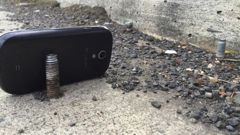 A bolt protruding from a road, close to the curb with a phone used to give scale