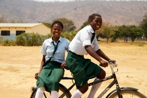 Girls in Africa riding a bicycle
