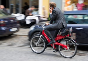 Cyclist wearing business suit riding through traffic while on phone