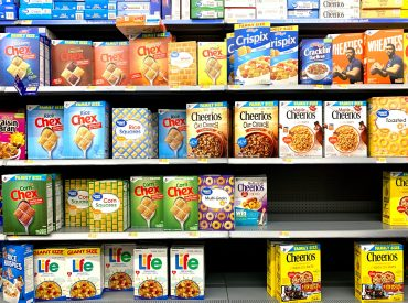 Supermarket row of cereal boxes. Shop by price per ounce.