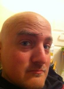 George with a hair clip in his bushy eyebrow