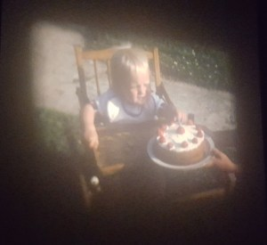 Photo of film of George aged 1 plucking strawberries from his birthday cake
