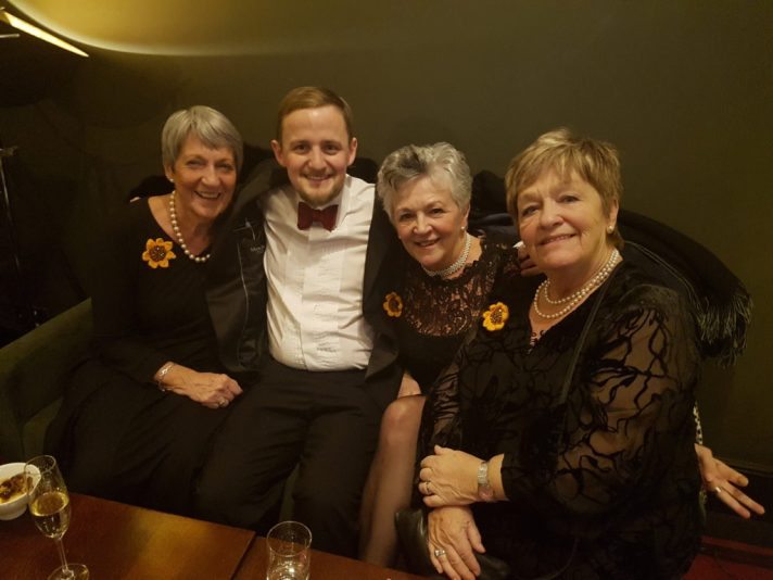 George on a sofa with three of the original Calendar Girls, wearing sunflowers