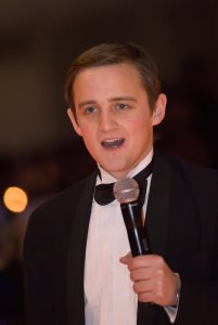 George with no beard, looking younger, but wearing black tie and talking into a microphone