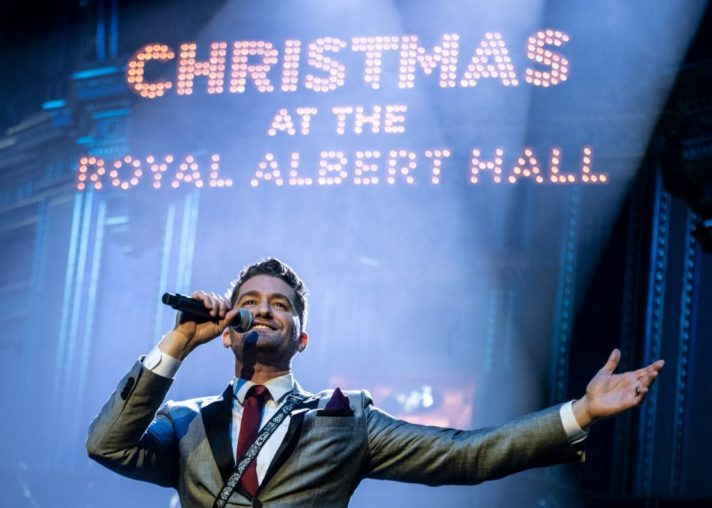 Glee actor/singer Matthew Morrison performing with CHRISTMAS AT THE ROYAL ALBERT HALL in lights behind him