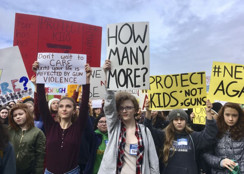 """A group of young people is gathered with signs reading """"How many more?"""" and """"Protect Kids not guns""""."""