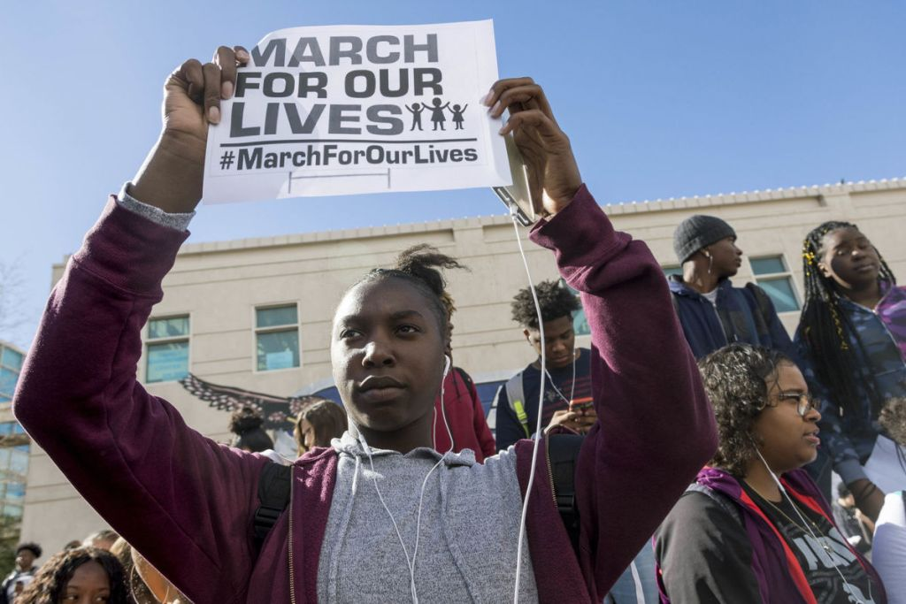 """A student holds a sign that reads """"MARCH FOR OUR LIVES"""" outside of a school"""