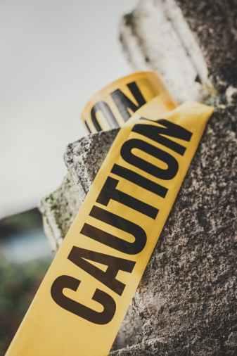 inscription caution on yellow tape on stone